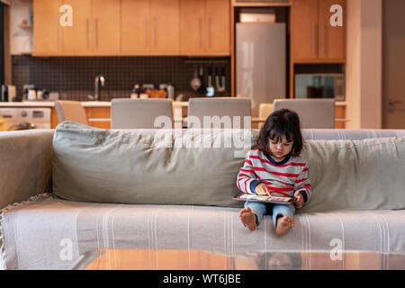 Carino piccola ragazza seduta sul suo divano utilizzando una compressa Foto Stock