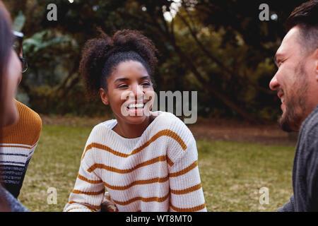 Ritratto di un sorridente giovane donna africana seduto e godendo con i suoi amici nel parco Foto Stock