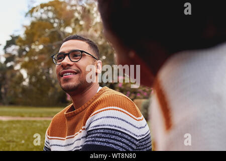 Close-up di un sorridente giovane africano indossando occhiali seduto con la sua fidanzata a park
