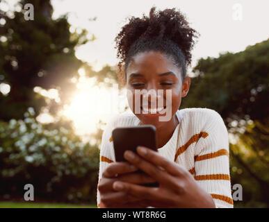 Ritratto di un americano africano giovane donna utilizzando il telefono cellulare nel parco sulla giornata di sole sorridenti - Molto donna felice sul cellulare Foto Stock