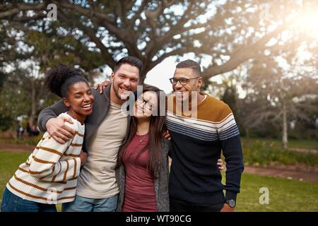 Sorridente gruppo di amici a ridere insieme mentre in piedi con le braccia intorno a ogni altro a un parco - happy gruppo di persone