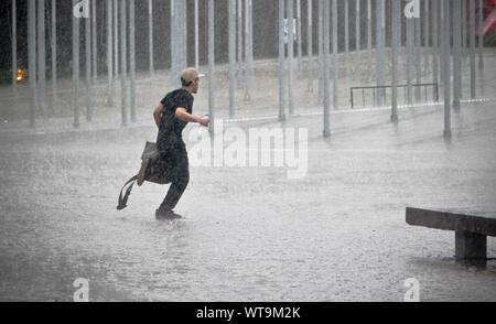 Uomo che corre sotto la pioggia sulla strada di città