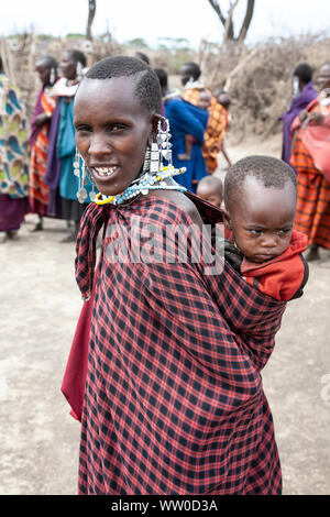 Maasai madre con un giovane bambino sulla schiena in un kraal Maasai in Tanzania