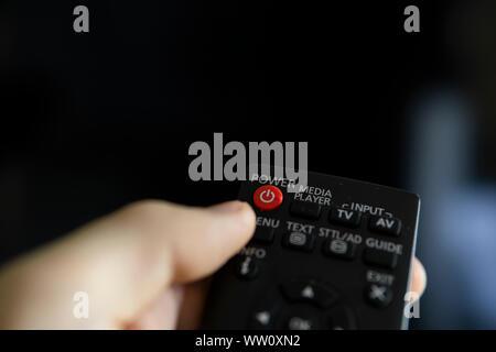 Chiudere in su su una mano d'uomo con il telecomando desidera accendere il TV e preme il pulsante sul telecomando. Telecomando in mano closeup. Foto Stock