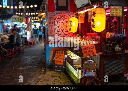 Taipei, Taiwan: piccola cucina di strada in stallo al Mercato Notturno di Raohe decorate con orange lanterne giapponesi, vendita di frutti di mare e birra di Taiwan