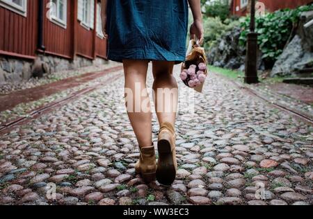 Le femmine le gambe a camminare su una strada acciottolata holding fiori Foto Stock