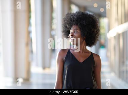 Sorridente giovane donna nera a piedi nella città guardando al lato, la bella giornata di sole