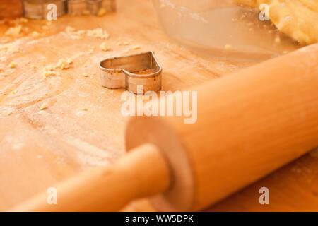 Cookie cutter a forma di cuore sul tavolo di legno accanto a pancake roll Foto Stock