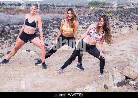 Tre giovani caucasici le donne a fare gli esercizi per un lifestyle fitness per rimanere heath con bel corpo. outdoor montare attività. allenamento in estate per le belle ragazze. gente allegra facendo stretching