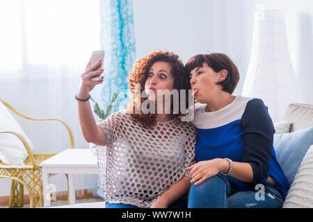 Due giovani donne a scattare foto con il cellulare a casa facendo bello e divertente di espressioni. migliori amici che l amore per comunicare in rete con gli amici. Foto Stock