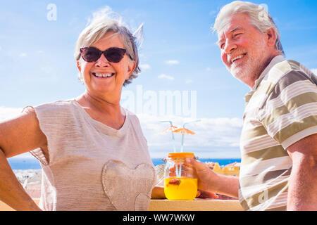 Coppia di anziani di età compresa tra bere succo di frutta sulla terrazza sul tetto con splendida vista sull'oceano. vacanza e concetto in pensione
