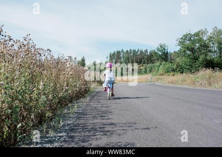 Vista posteriore di una giovane ragazza in bicicletta a casa da scuola lungo la strada di campagna Foto Stock