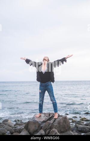Indie caucasico giovane donna in piedi con le braccia aperte e godersi la natura e la libertà da solo sulle rocce in spiaggia, sull'oceano in background, abiti casual e wanderlust concept Foto Stock