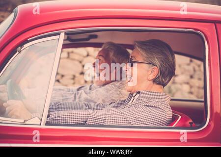 Anziana coppia senior con cappello, con occhiali, con il grigio e il bianco dei capelli, con camicia casual, su vintage auto rossa in vacanza godendosi il tempo e la vita. Con un allegro telefono cellulare sorridente e going crazy insieme
