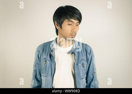 Uomo asiatico in jeans e camicia con pan in disordine