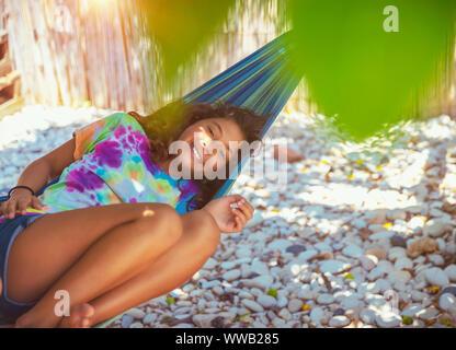 Ritratto di una bambina di riposo in amaca sulla spiaggia, con il piacere di trascorrere del tempo in Summer Camp vicino al mare, godendo di felice vacanze attive Foto Stock