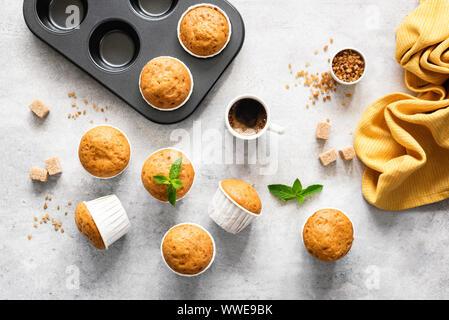 In casa deliziosi muffin vegetariano con lo zucchero di canna sul cemento grigio Sfondo, piana, laici vista superiore