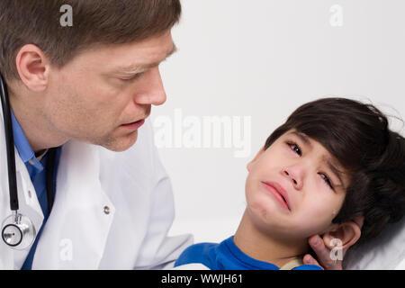Medico di sesso maschile nei primi anni quaranta consolante cinque anni paziente disabilitato durante la visita di office Foto Stock