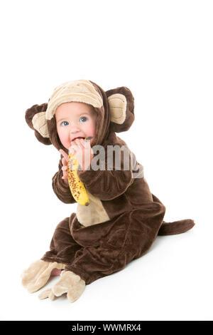 Bambino in costume di Scimmia banane di contenimento Foto Stock