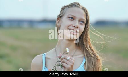Ritratto di un giovane sorridente sedici-anno-vecchia ragazza con un fiore a margherita nelle sue mani. Bionda con capelli lunghi. Foto Stock