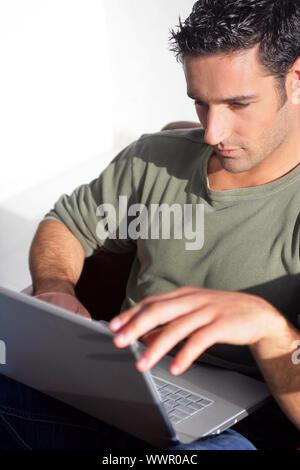 Dai capelli scuri uomo seduto con il computer portatile