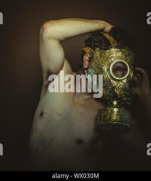 Uomo di inquinamento con oro maschera a gas e di arabeschi in pose di annegamento e disperazione, depressione e psichiatria concetto.