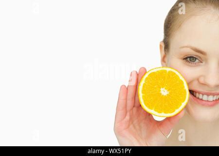 In prossimità di una donna in possesso di un arancione nella sua mano contro uno sfondo bianco Foto Stock