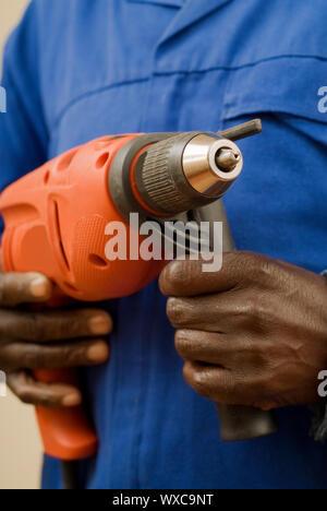 African American lavoratore edile azienda strumento di potere nelle mani di Foto Stock