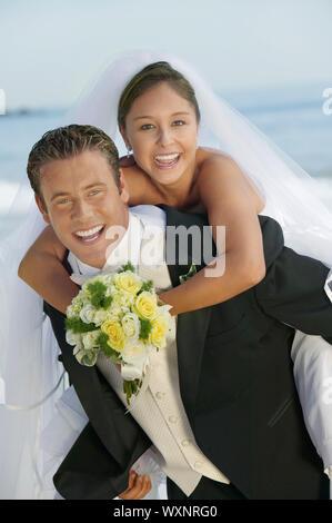 Lo sposo che sposa un piggyback Ride Foto Stock