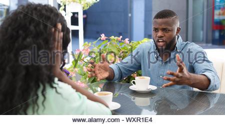 L'uomo urlando e sostenendo con una donna in cafe Foto Stock