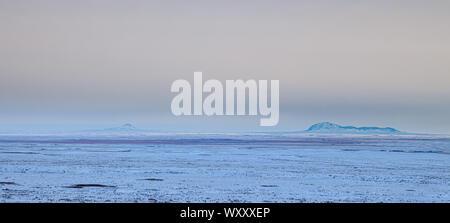 Vista in lontananza le dolci colline di erba nel nord del Montana, USA, in un freddo inverno di sera