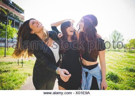 Tre giovani amici di sesso femminile ridere insieme in posizione di parcheggio Foto Stock