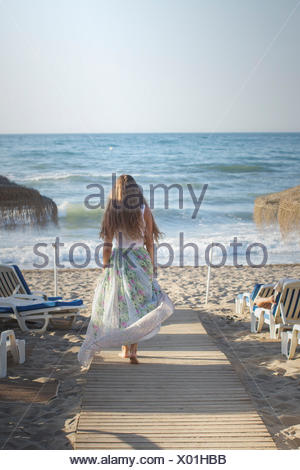 Giovane donna camminare lungo la passerella di legno verso la spiaggia Foto Stock