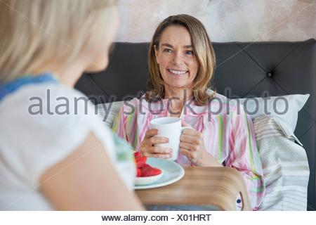 Senior donna sorridente alla figlia mentre un caffè a letto Foto Stock