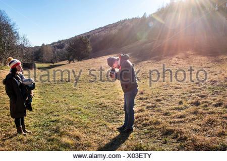 L'uomo prendendo fotografia di donna e bambino utilizzando fotocamera medio formato, in ambiente rurale, Italia