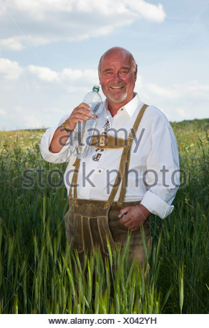Uomo anziano che indossa un tradizionale paio di pantaloni e tenendo una bottiglia di acqua nelle sue mani in un campo di mais Foto Stock