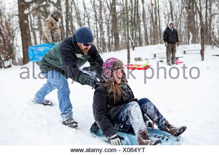 Metà adulto giovane e figlio adolescente giocando su slittini Foto Stock