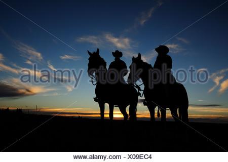 Un cowgirl e un cowboy seduti sulle loro cavalli al tramonto, Saskatchewan, Canada Foto Stock