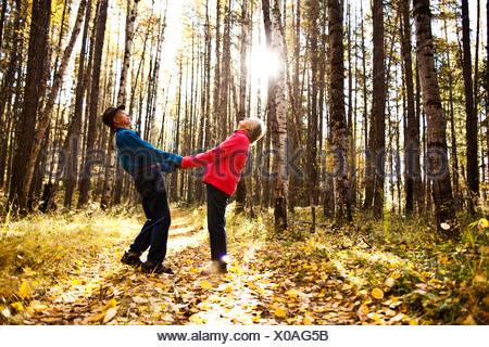 Una felice coppia in pensione a ridere e sorridere mentre su una escursione attraverso una foresta durante la caduta in Idaho.