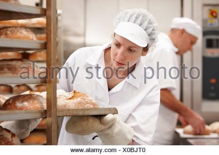 Lo chef che porta il vassoio del pane in cucina Foto Stock