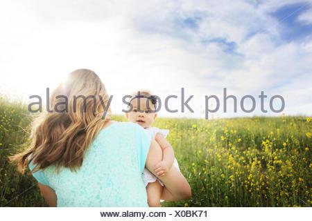 Vista posteriore della donna che cammina in campo e tenendo la sua bambina Foto Stock