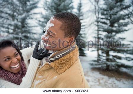 Allegro giovane avente lotta con le palle di neve in inverno Foto Stock