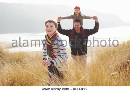 Padre e figli a piedi attraverso le dune sulla Spiaggia Invernale Foto Stock