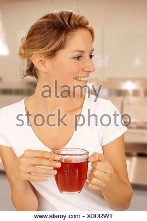 La donna in cucina a bere il tè di frutta Foto Stock