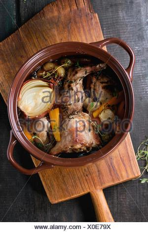 Brown vaso di ceramica con stufato di coniglio con bouillon, le verdure e le erbe aromatiche, servita sul tagliere di legno su un vecchio tavolo di legno. R Foto Stock