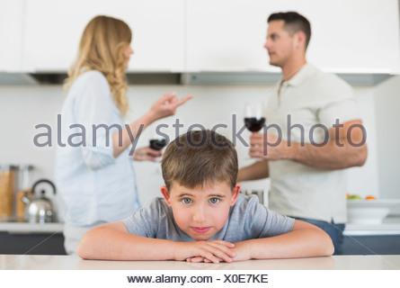 Triste ragazzo appoggiata sul tavolo mentre i genitori sostenendo Foto Stock