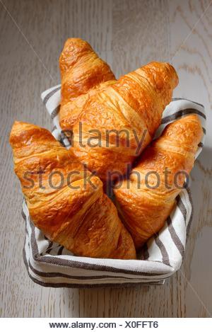 Croissant in un cestino sul tavolo. Foto Stock