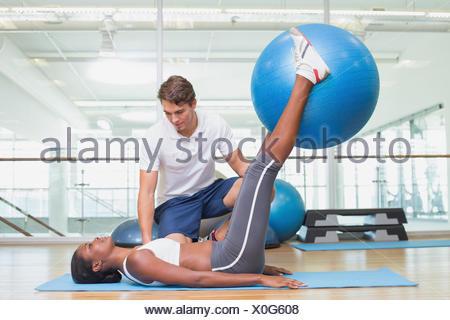 Personal trainer lavora con il cliente tenendo palla ginnica Foto Stock