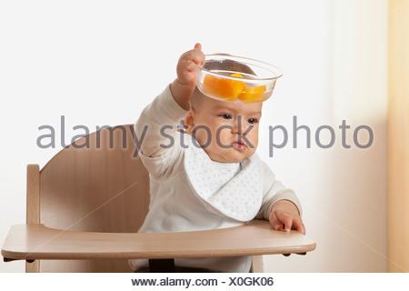 Ritratto di bambino in sedia alta tenendo la coppa con frutta Foto Stock