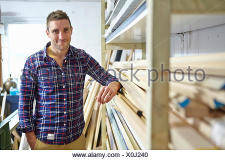 Ritratto di metà uomo adulto addossato a ripiani in picture corniciai workshop Foto Stock